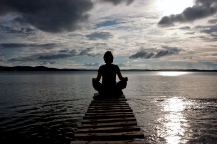 Person meditating at the end of a dock on the ocean